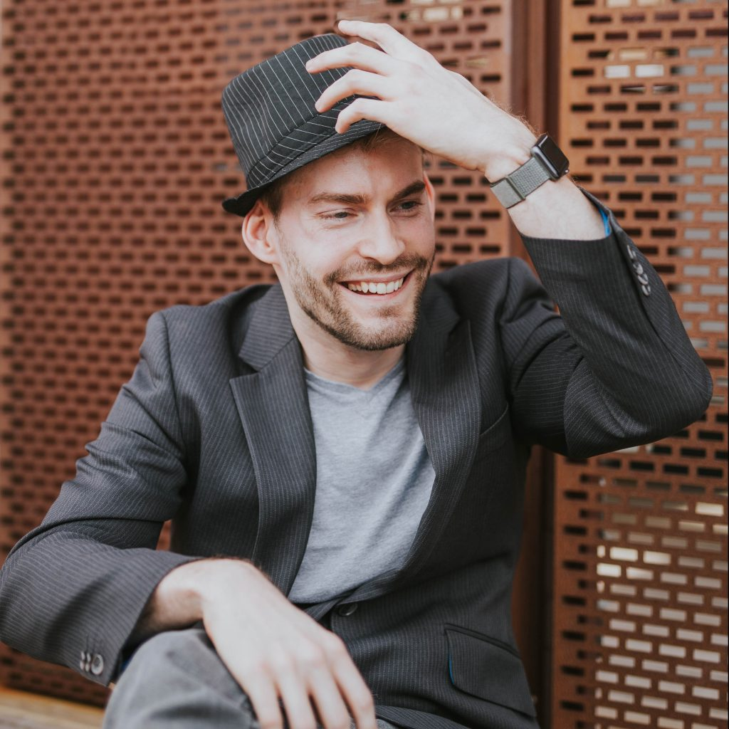 A picture of Dan wearing a suit jacket and trilby hat smiling